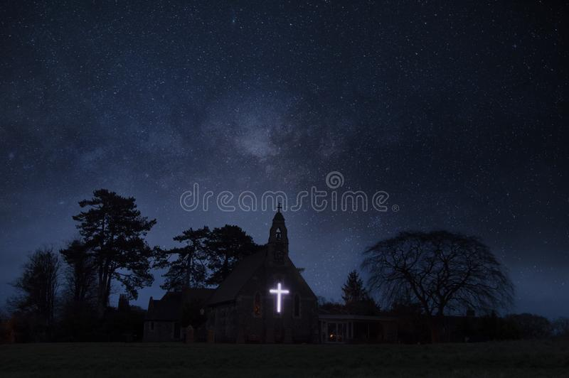 Een atmosferisch concept geeft van een kerk met een gloeiend kruis uit onder een sterrige hemel bij nacht stock foto's