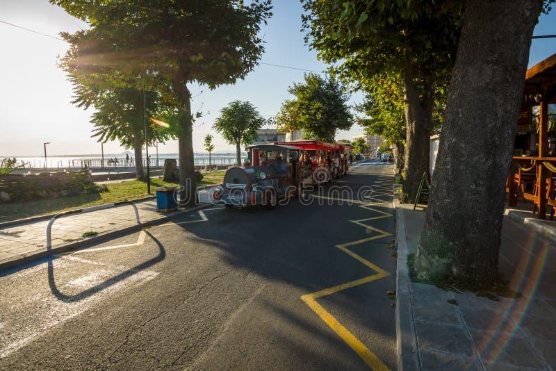 Een auto met een aanhangwagen, in de vorm van een locomotief en passagiersbussen op de dijk van de kuststad van Pomorie stock afbeeldingen