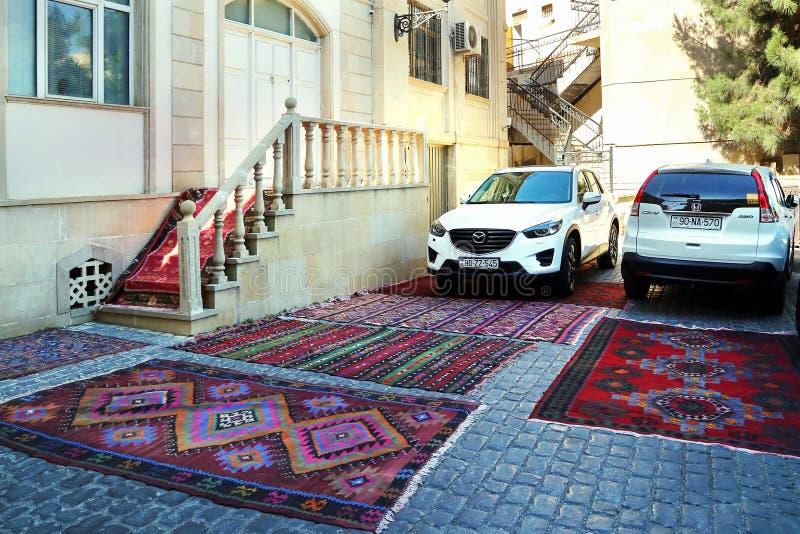Een auto op een tapijt voor verkoop in de oude stad van Icheri Sheher wordt geparkeerd die Toon zo de kwaliteit van aan stock foto