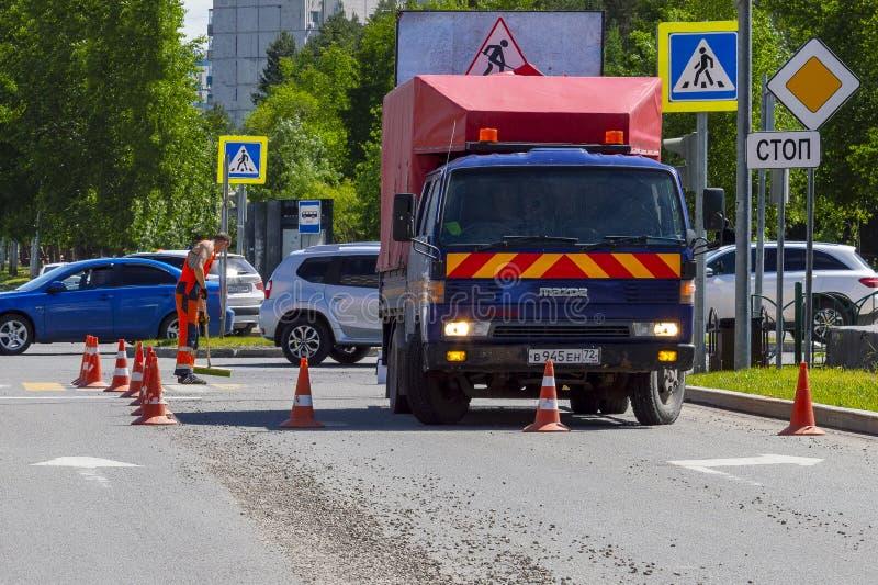 Een auto van de wegreparatie en een mannelijke arbeider merken omhoog op het asfalt royalty-vrije stock afbeelding