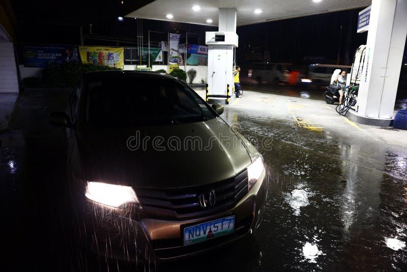 Een auto wordt bij een benzine geparkeerd die post op een regenachtige nacht opnieuw vullen stock fotografie