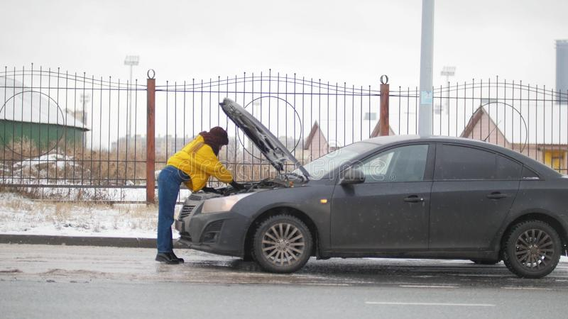 Een autoongeval Een jonge vrouw die zich door een gebroken auto bevinden Het zoeken van een storing stock fotografie