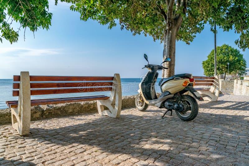 Een autoped naast een bank en een boom met zien op de achtergrond Reis en avonturenconcept Een een autopedreis en avontuur stock fotografie