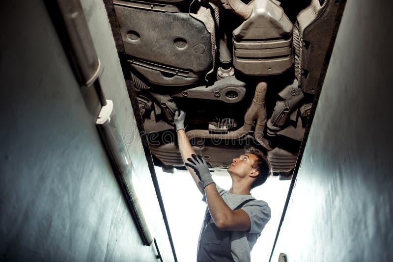 Een autowerktuigkundige controleert een opgeheven auto Autoonderhoud stock foto's