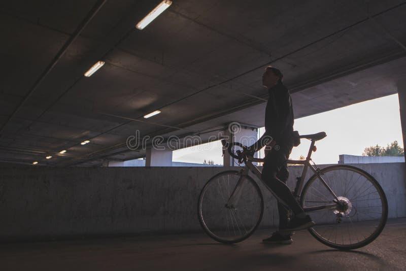 Een avondfoto van een jonge fietser die zich onder de brug met een fiets bevinden stock fotografie