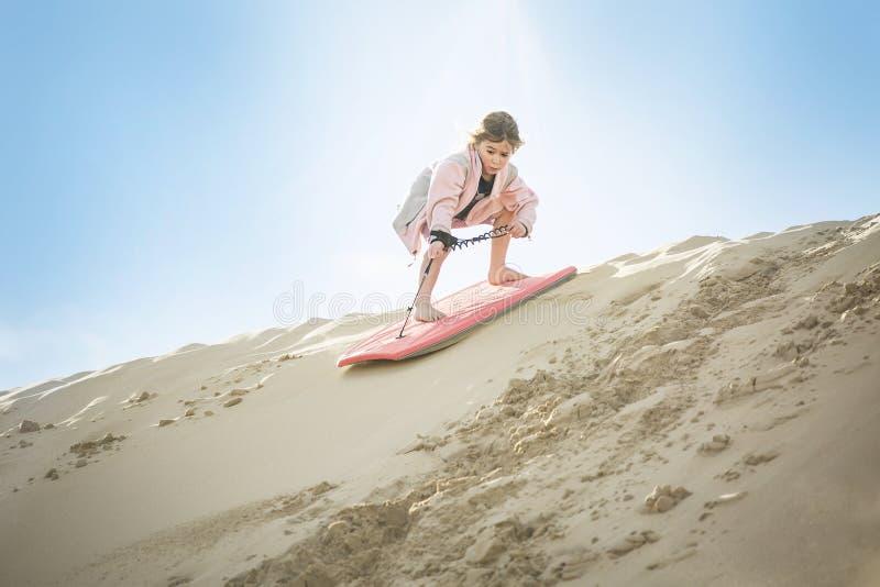 Een avontuurlijk Meisje die onderaan de Zandduinen inschepen stock foto