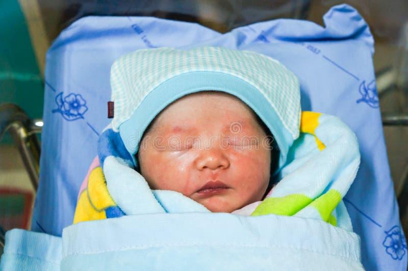 Een Aziatisch babymeisje, leuke gezichtsslaap goed met dekking de deken stock foto
