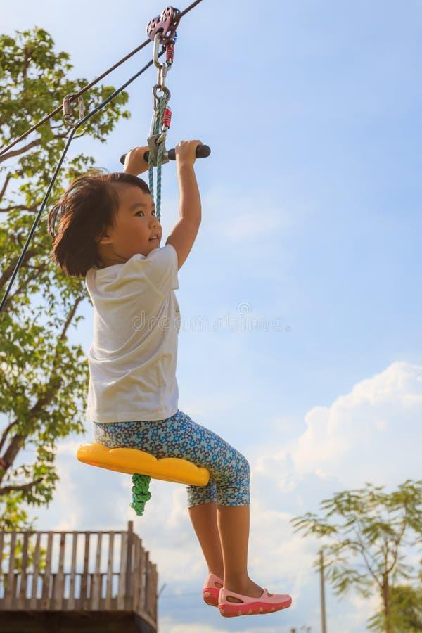 Een Aziatisch klein meisje speelt kabel het vliegen stock foto's