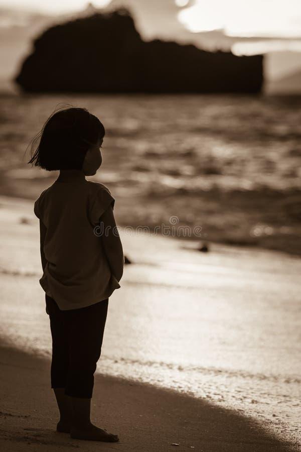 Een Aziatisch meisje die zich alleen op het strand bevinden stock afbeelding