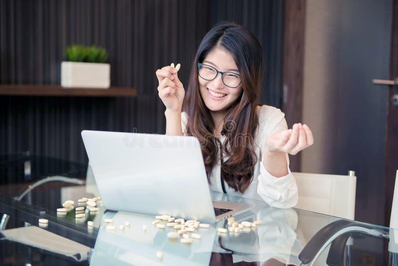Een Aziatische bedrijfsvrouw die drugs gebruiken terwijl het werken royalty-vrije stock foto's
