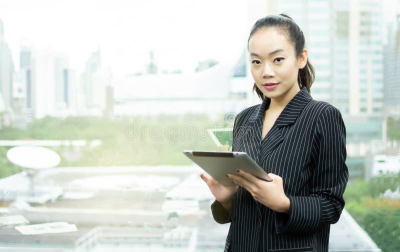 Een Aziatische bedrijfsvrouw gebruikt tablet naast venster stock foto