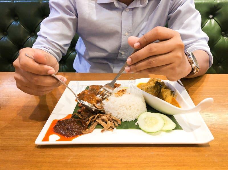 Een Aziatische lepel en een vork van de mensenholding, die reeks van heerlijk van de rijst van de kippenkerrie met de sambal van  stock fotografie