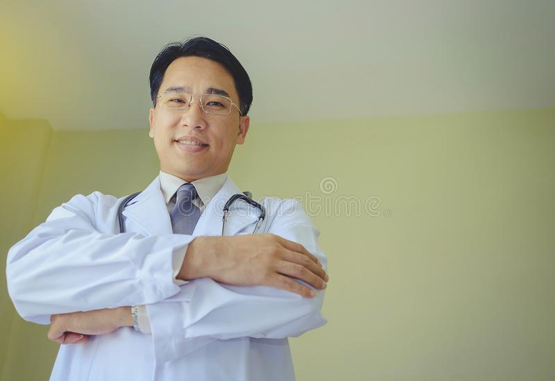 Een Aziatische mannelijke arts bevindt zich glimlachend, vriendschappelijk en vriendelijk royalty-vrije stock fotografie