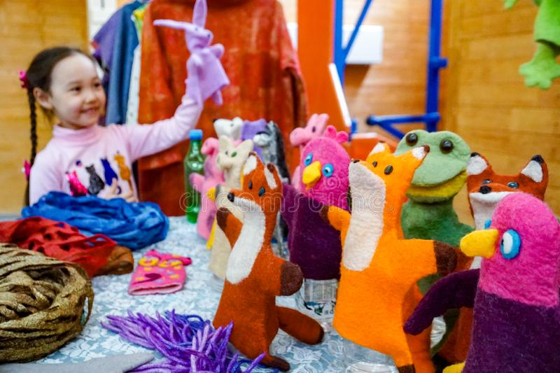 Een Aziatische meisjesspelen van de schoolleeftijd met een poppenpoppentheater stock afbeelding