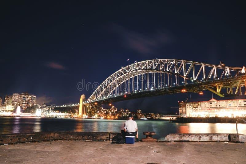 Een Aziatische mens die bij pijler twee 2, de rots bij nacht in S vissen stock afbeeldingen