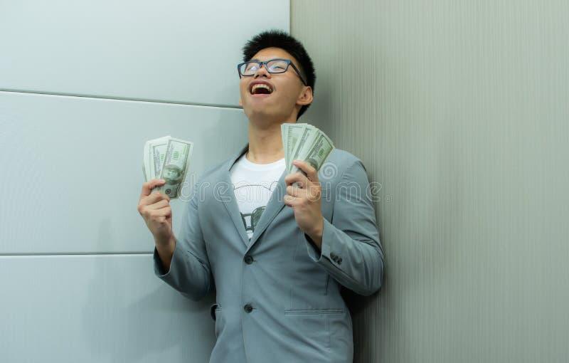 Een Aziatische mens is gelukkig om heel wat bankbiljetten te houden stock foto