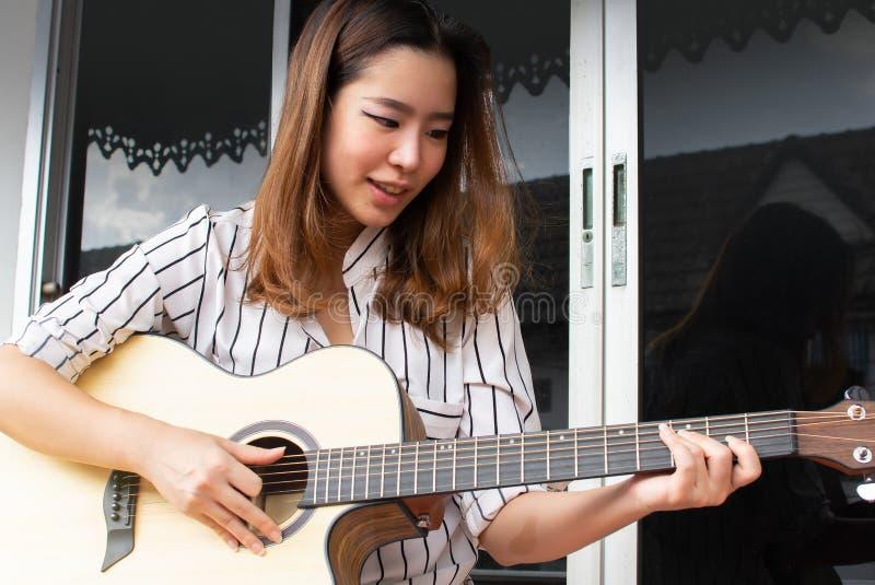 Een Aziatische mooie vrouw speelt gitaar stock afbeelding