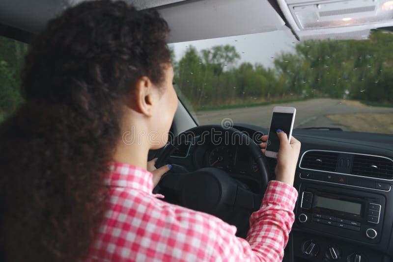 Een Aziatische vrouw gebruikend en bekijkend slimme telefoon in een auto op de weg royalty-vrije stock foto