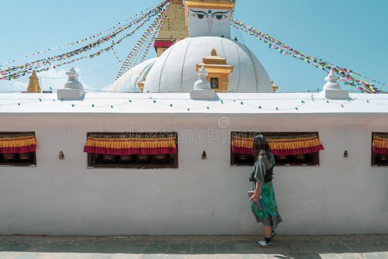 Een Aziatische vrouwentoerist raakt de klok binnen de muur van Boudhanath Stupa en biddend krijg zegen stock afbeelding
