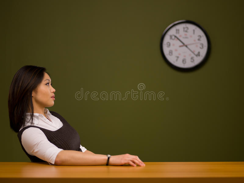 Een Aziatische vrouwenzitting bij een bureau stock fotografie