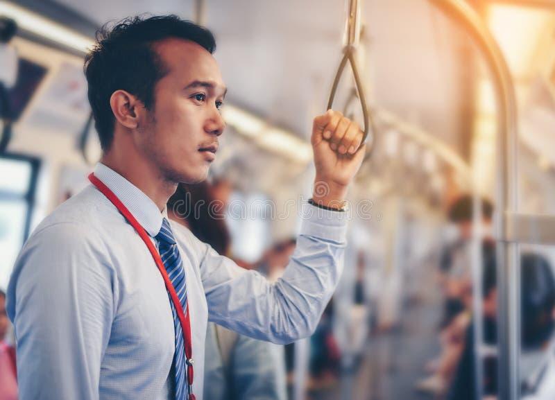 Een Aziatische zakenman reist een openbare trein stock fotografie