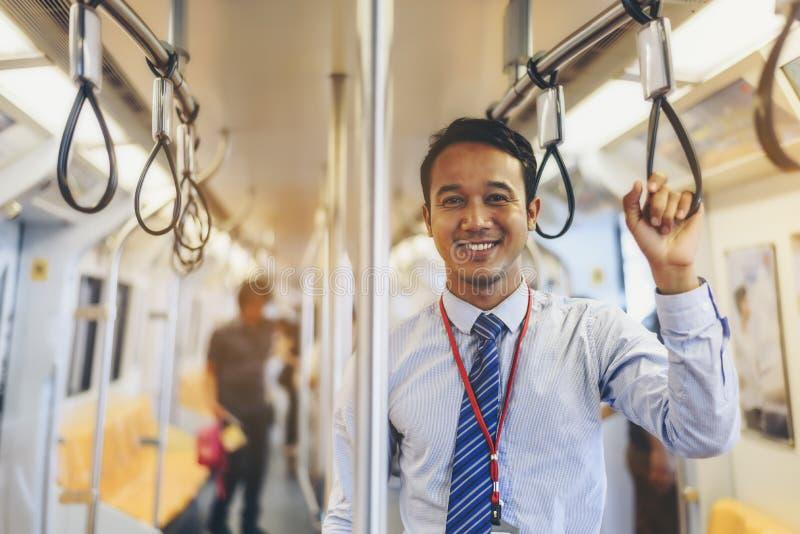 Een Aziatische zakenman reist een openbare trein stock afbeelding