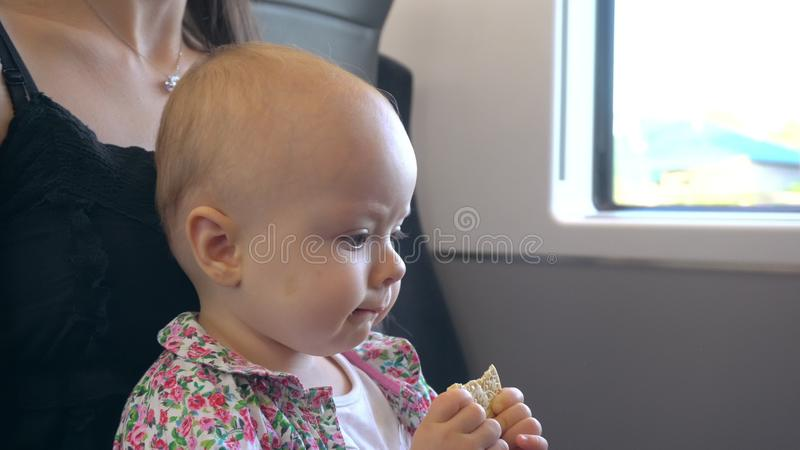 Een Baby die een Koekje op de Trein eten stock afbeeldingen