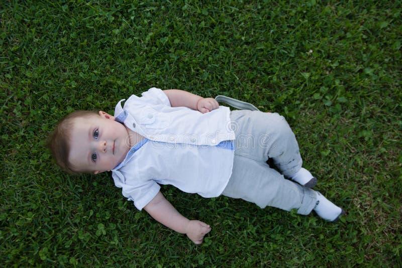 Een baby die op het gras leggen, die leuke buiktijd hebben, weinig babyjongen stock afbeeldingen