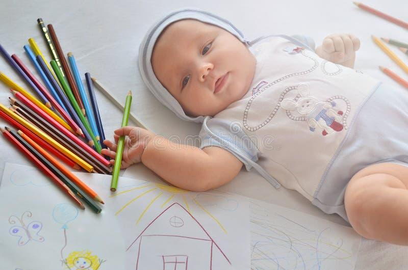 Een baby met potloden Het kind trekt royalty-vrije stock afbeelding