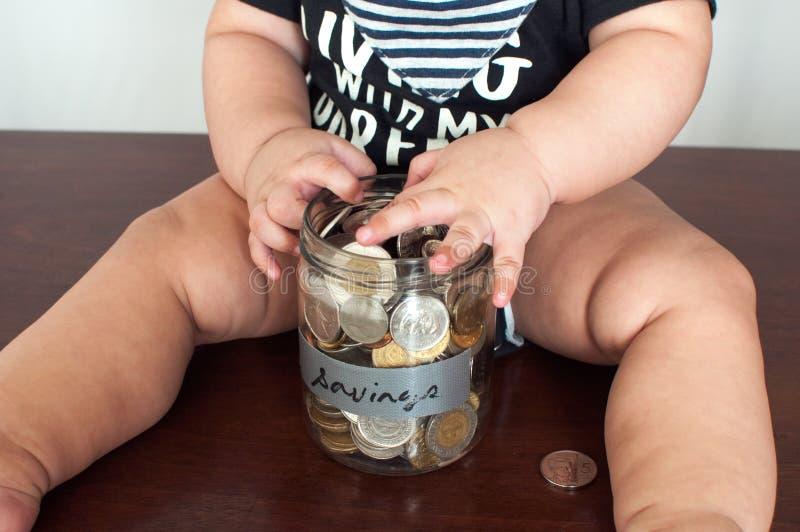 Een babyjongen houdt een kruik met muntstukken wordt gevuld dat royalty-vrije stock fotografie