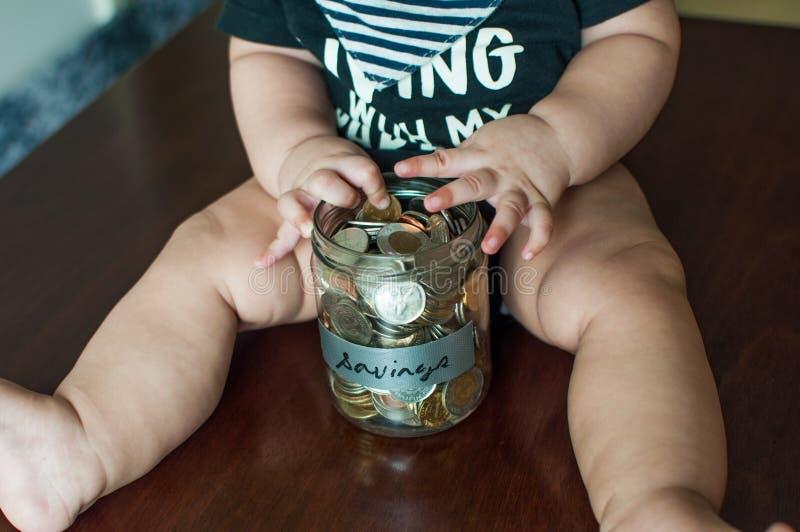 Een babyjongen houdt een kruik met muntstukken wordt gevuld dat stock foto
