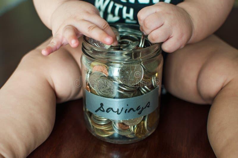 Een babyjongen houdt een kruik met muntstukken wordt gevuld dat royalty-vrije stock afbeeldingen