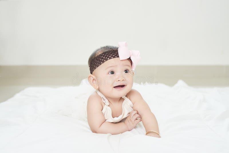 Een babymeisje kruipt langs de vloer met een nieuwsgierige blik op haar gezicht Horizontaal schot stock afbeeldingen