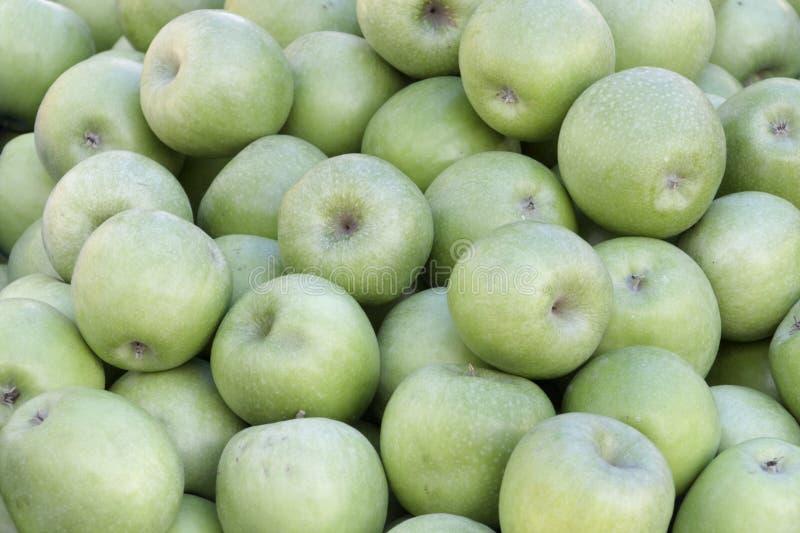 Een backround van veel groene appelen stock foto's
