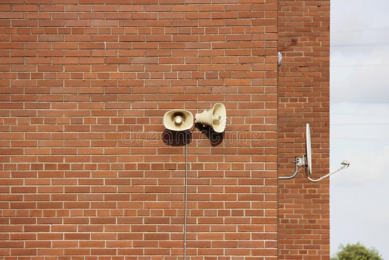 Een bakstenen muur van een woningbouw, twee luidsprekers en een satellietschotel tegen de hemel royalty-vrije stock foto