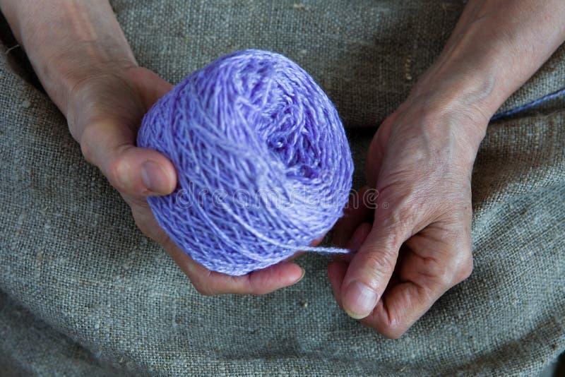 Een bal van draad in de handen van een bejaarde royalty-vrije stock afbeelding