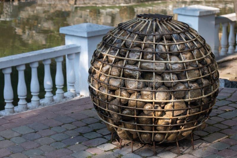Een bal van metaalstaven met stenen tegen een witte omheining worden gevuld die royalty-vrije stock afbeeldingen