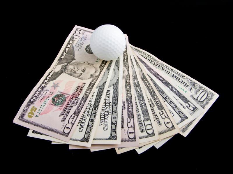 Een bal voor golf ligt op dollarnota's royalty-vrije stock afbeelding