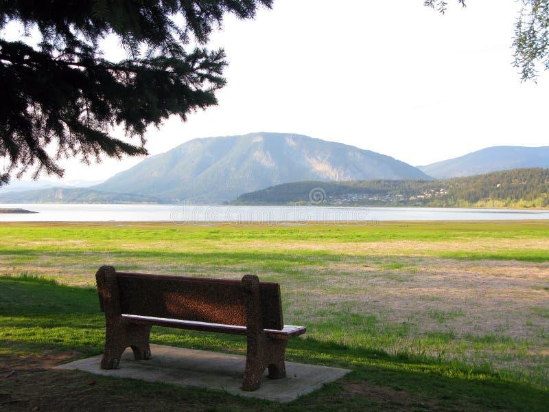 Een bank op mooi toneelgebied van meer en berg stock fotografie