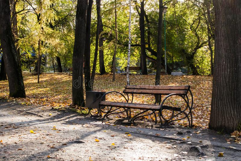 Een bank in een oud herfstpark in de stad royalty-vrije stock afbeelding