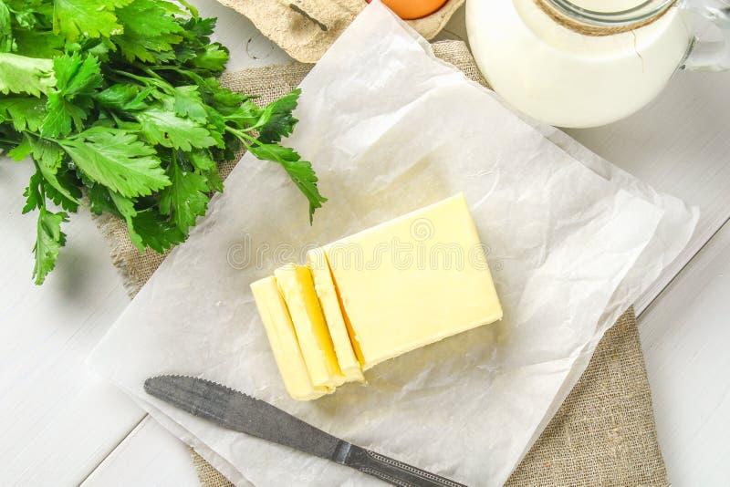 Een bar van boter wordt gesneden in stukken op een houten die raad met een mes, door melk wordt omringd, eieren en peterselie op  stock afbeelding