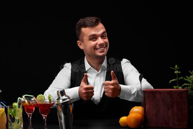 Een barman toont grote duimen, een barteller met sinaasappelen, citroen, een schudbeker, de glazen van Margarita op zwarte achter royalty-vrije stock fotografie