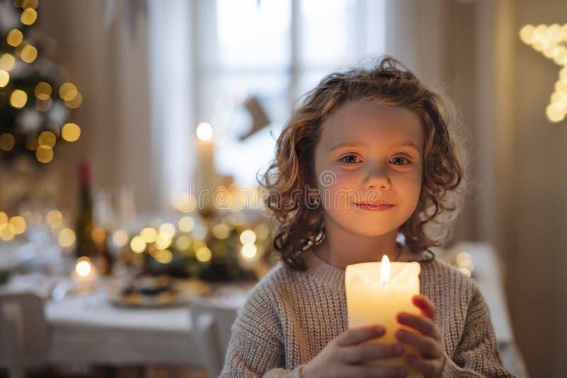 Een beangstigend klein meisje dat met Kerstmis binnen staat en kaars vasthoudt royalty-vrije stock fotografie