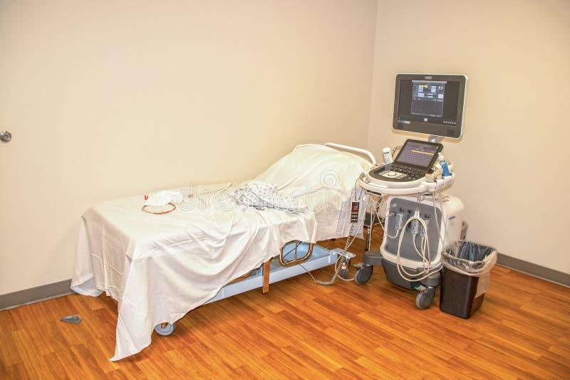 Een bed en machines om een hartpatiënt een echocardiogram te geven - het ziekenhuistoga en elektroden en draden die op bed leggen royalty-vrije stock afbeeldingen