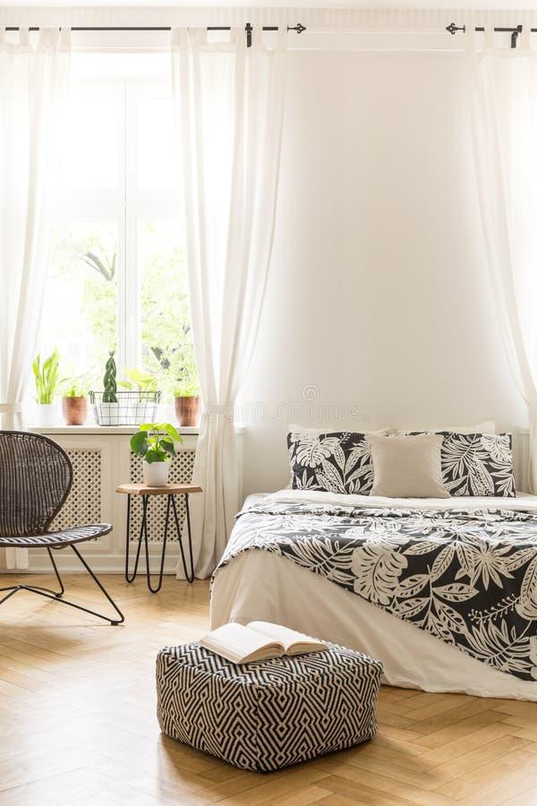 Een bed met het linnen van het bladdecor, een rotan en een metaal zitten en een poef voor royalty-vrije stock afbeelding