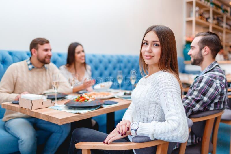 Een bedrijf van mensen brengt tijd in een koffie, het babbelen, het eten en het drinken door stock afbeelding
