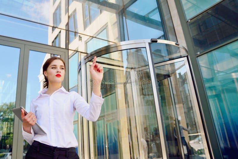 Een bedrijfsdame met een tablet in haar hand klikt op virtueel Di stock afbeelding