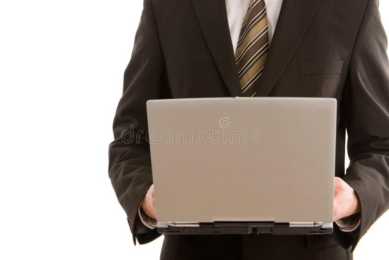 Een bedrijfsmens die zilveren laptop houdt stock afbeelding