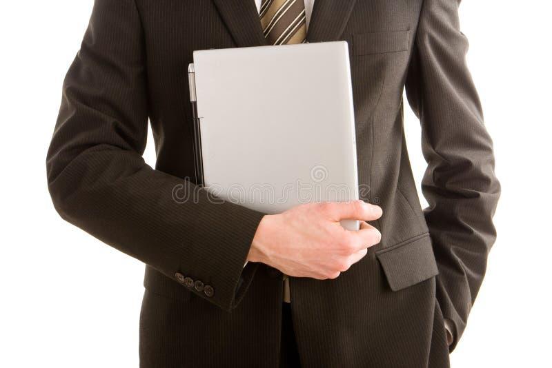 Een bedrijfsmens die zilveren laptop houdt stock foto