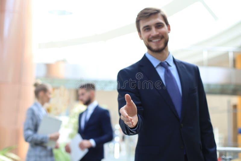 Een bedrijfsmens met een open hand klaar om een overeenkomst te verzegelen stock foto